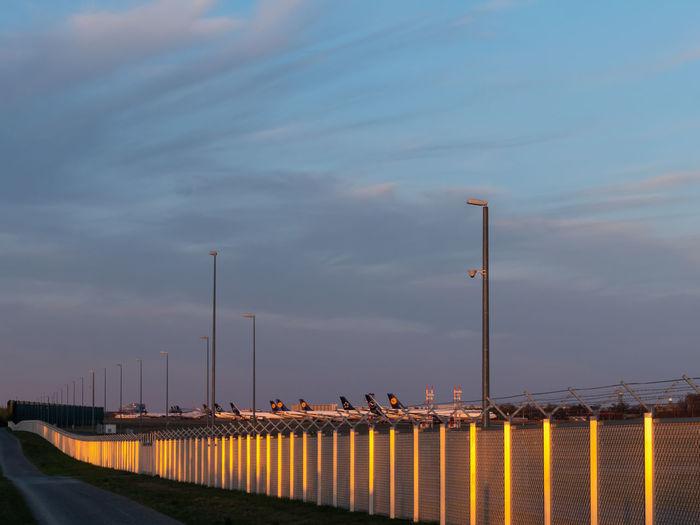 Street lights by bridge against sky at dusk