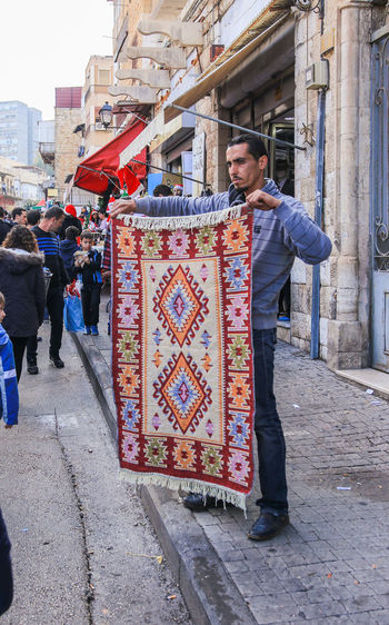 Haifa, Israel - December 17, 2016 : Carpet Seller sells to customers handmade carpets at the Christmas market in the German Colony in Haifa, Israel Carpet Christmas City City Life Colony Cultures Customer  Day December Decoration Festive German Haifa Handmade Israel Market Men Outdoors People Seasonal Seller Shop Store Street Traditional