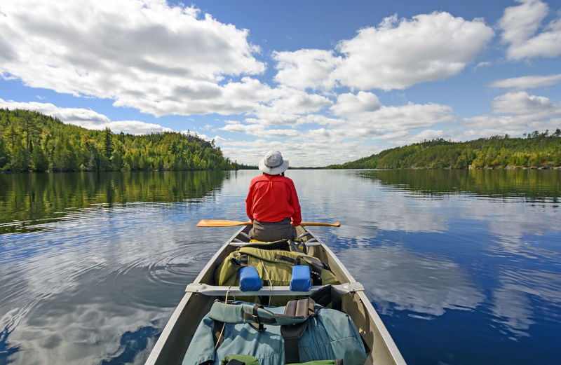 Rear view of man sitting on boat in lake against sky