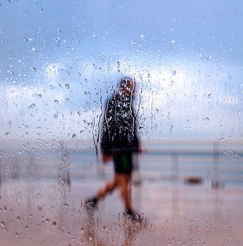 Rear view of man walking on wet window in rainy season