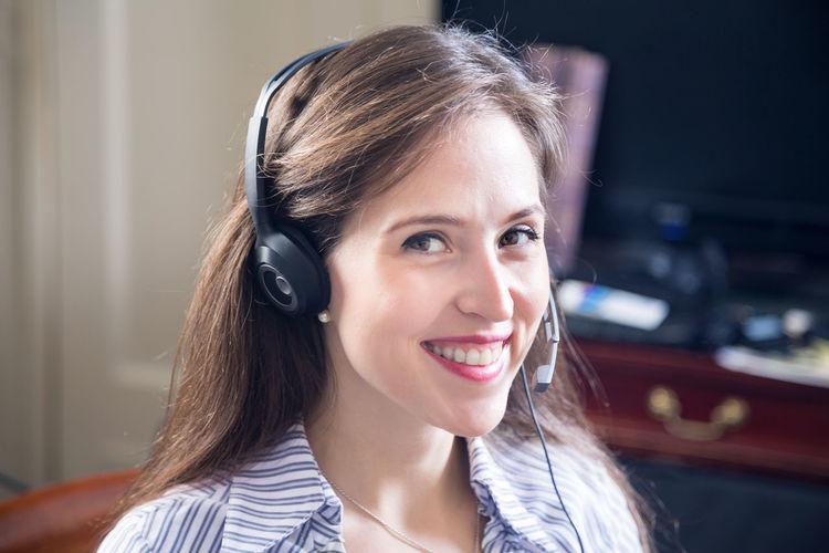 Portrait of smiling female customer service representative answering calls in office