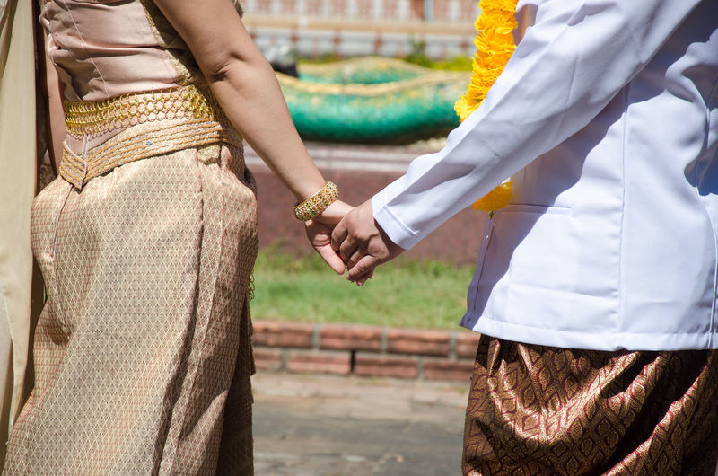 Midsection of couple holding hands while standing on footpath