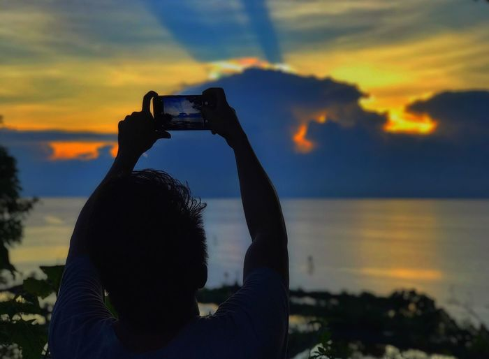 Be. Ready. Photography Themes Sunset Real People Smart Phone Wireless Technology Silhouette Holding Technology Sky Camera - Photographic Equipment Mobile Phone Focus On Foreground Leisure Activity Portable Information Device Cloud - Sky Digital Camera Outdoors Lifestyles One Person