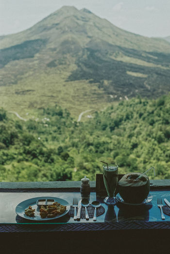 Having lunch over looking Mount Agong, Bali Bali INDONESIA Mount Agung Beauty In Nature Close-up Coffee - Drink Day Drink Film Photography Food Food And Drink Freshness Indoors  Landscape Mountain Mountain Range Nature No People Plate Ready-to-eat Refreshment Scenics Table Tea - Hot Drink Tree