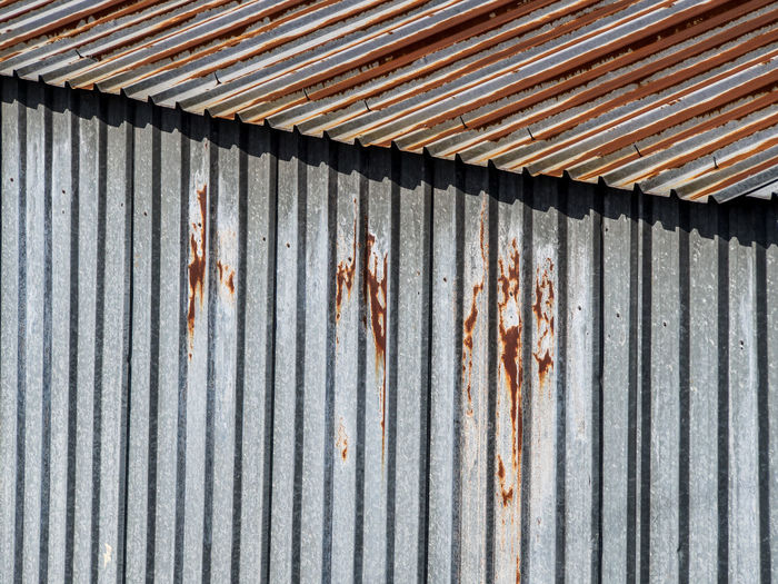 Rusty corrugated iron hut Corrugated Iron Iron Metal Corrugated No People Pattern Rusty Roof Architecture Day Built Structure Full Frame Weathered Textured  Building Exterior Striped Wall - Building Feature Damaged Outdoors Old Sheet Metal Garage Roof Tile Hut Shed