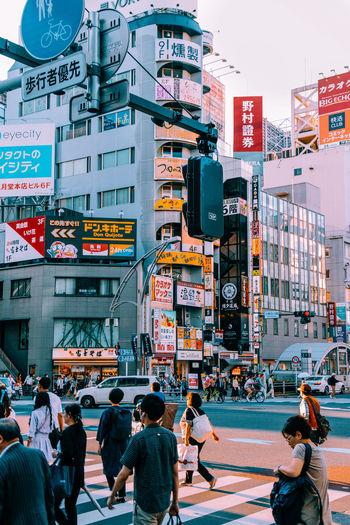 People walking on street by buildings in city