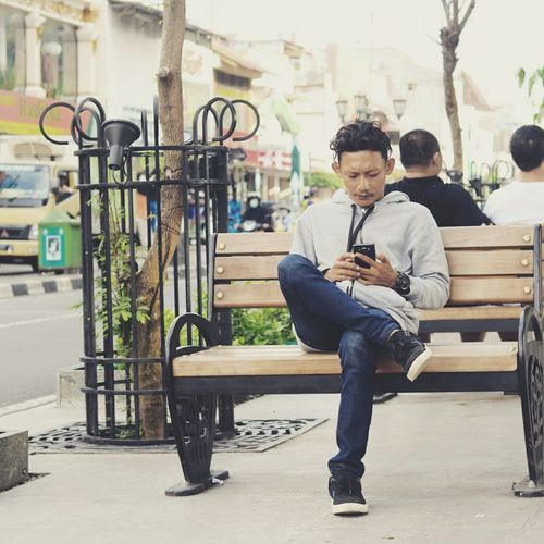 Man and woman sitting on bench in city