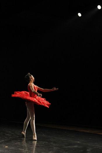 Full length of woman dancing against black background