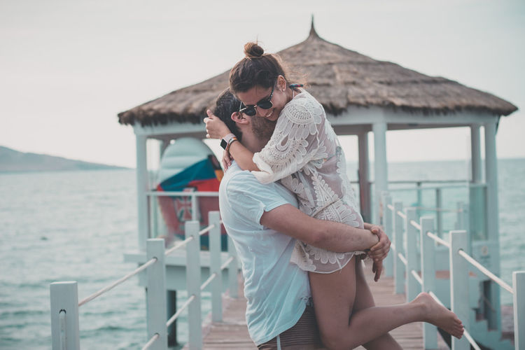 Loving Boyfriend Carrying Girlfriend While Standing On Pier