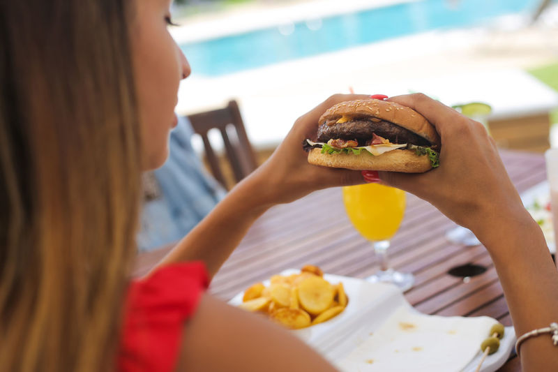 Midsection of woman eating food in restaurant