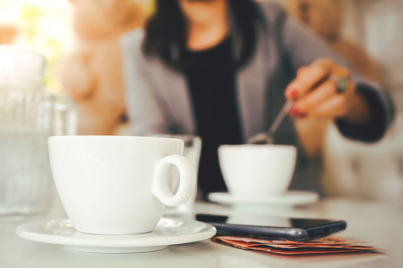 Coffee cup on table in cafe shop. Woman having chill time with coffee in coffee shop. Adult Cafe Coffee Coffee - Drink Coffee Cup Crockery Cup Drink Focus On Foreground Food And Drink Holding Indoors  Lifestyles Midsection Mug One Person Real People Refreshment Saucer Table Tea Cup Women