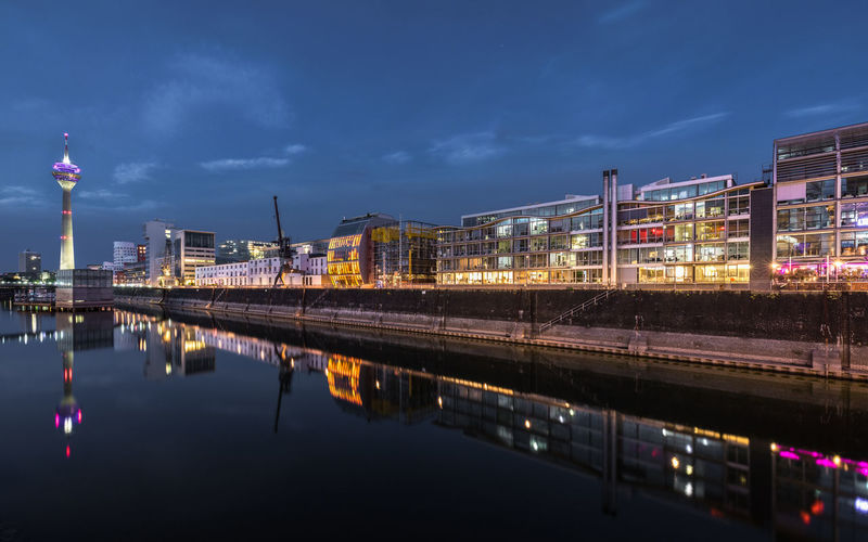 Reflection of illuminated buildings in river against sky