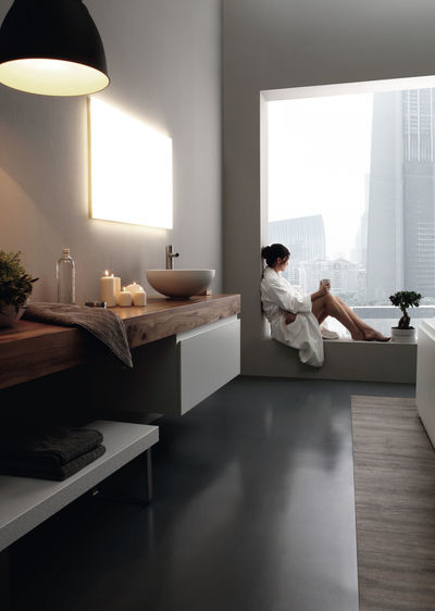 Woman sitting on window sill in bathroom