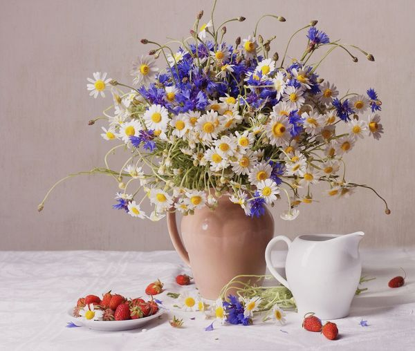 Flower Vase With Strawberries In Plate On Table Against Wall