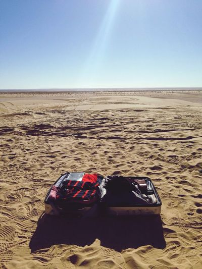 Open Luggage On Sand At Beach Against Sky