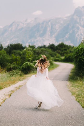 Rear view of bride running on road