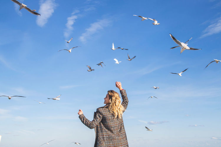 Rear view of woman standing against birds flying in blue sky