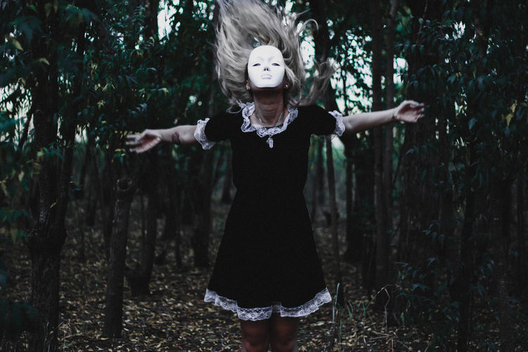 Woman wearing mask with arms outstretched standing in forest