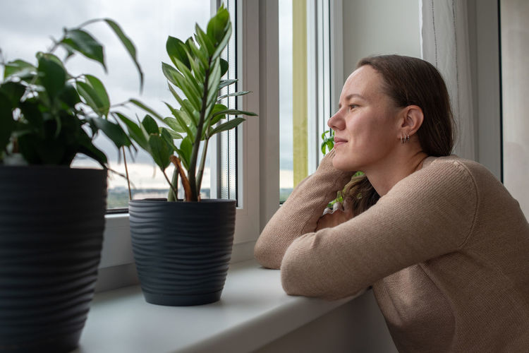 Side view of smiling woman looking through window at home