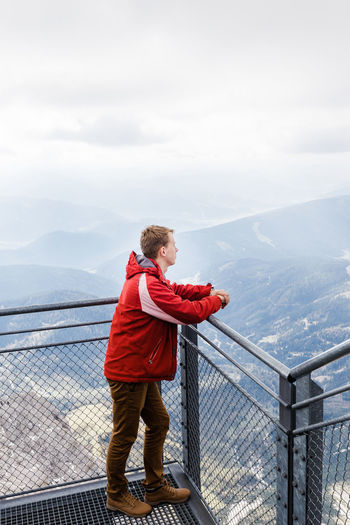 Man standing on railing against mountain