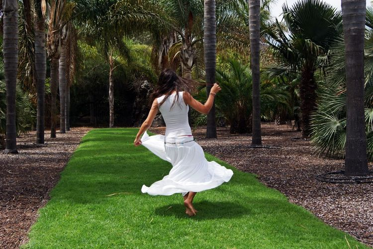 Rear view of woman dancing on grassy pathway by palm trees
