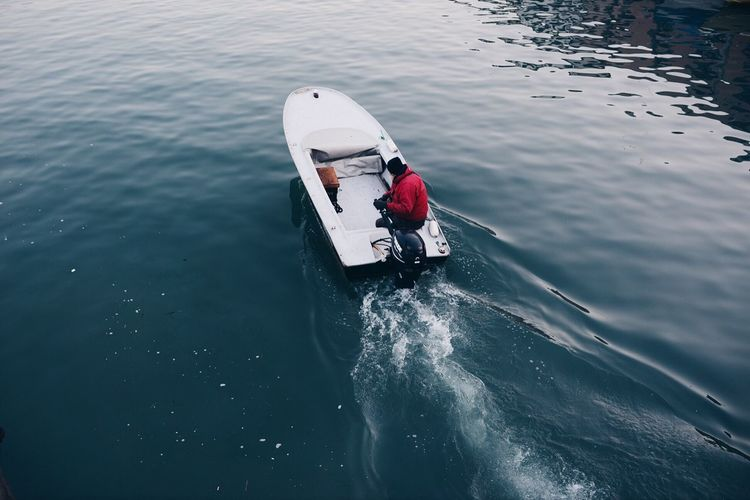 High Angle View Of Man Sailing Motorboat On Lake