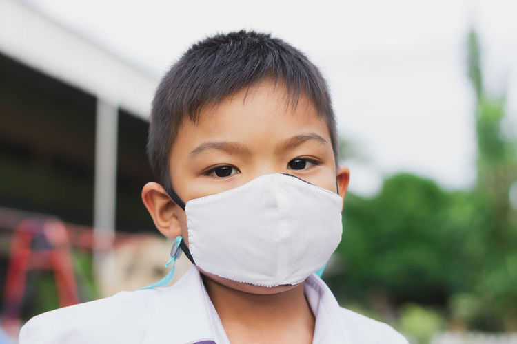 Close-up portrait of boy wearing mask outdoors