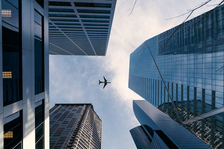 Low angle view of airplane flying over skyscrapers against sky