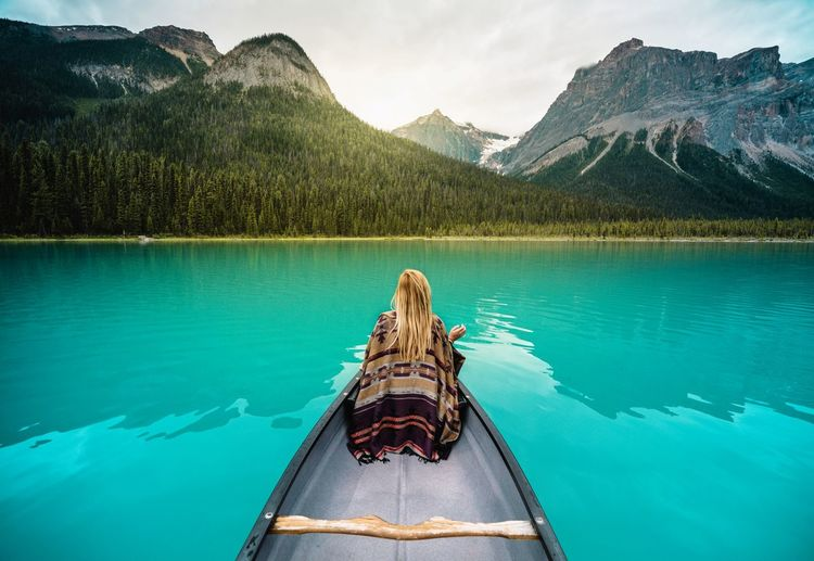 Rear View Of Woman Sitting In Boat On Lake Against Mountains