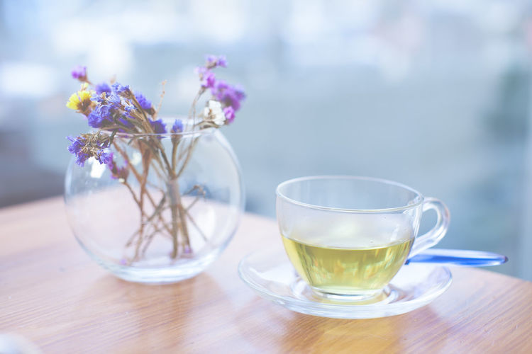 Close-up of herbal tea and flower pot on table at cafe