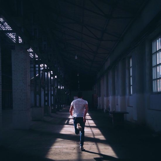 Full Length Rear View Of Man Running In Building On Sunny Day