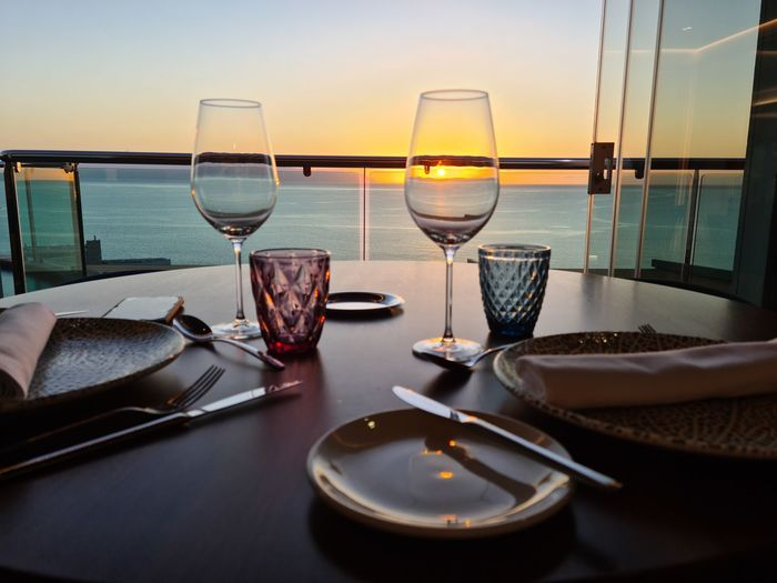 High angle view of beer on table against sea during sunset