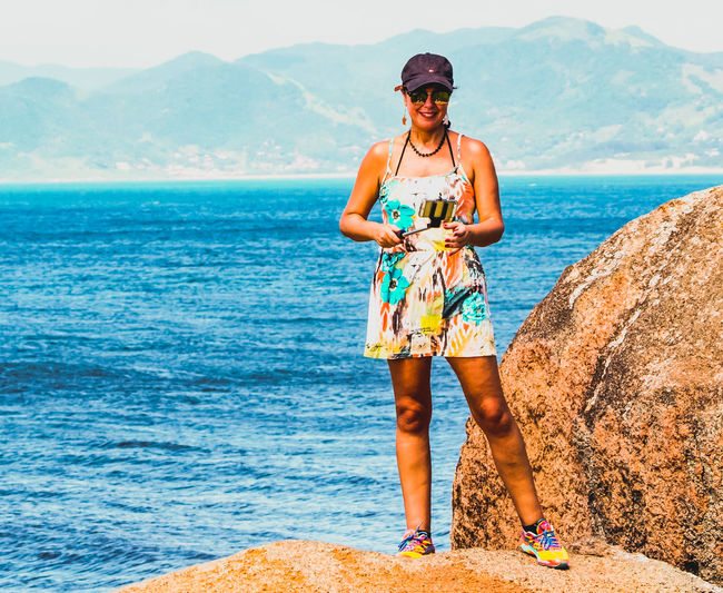 Full Length Of Woman Standing On Rock Against Sea