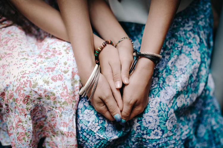 Hands of mom and daughter with boho bracelets. family and love concept