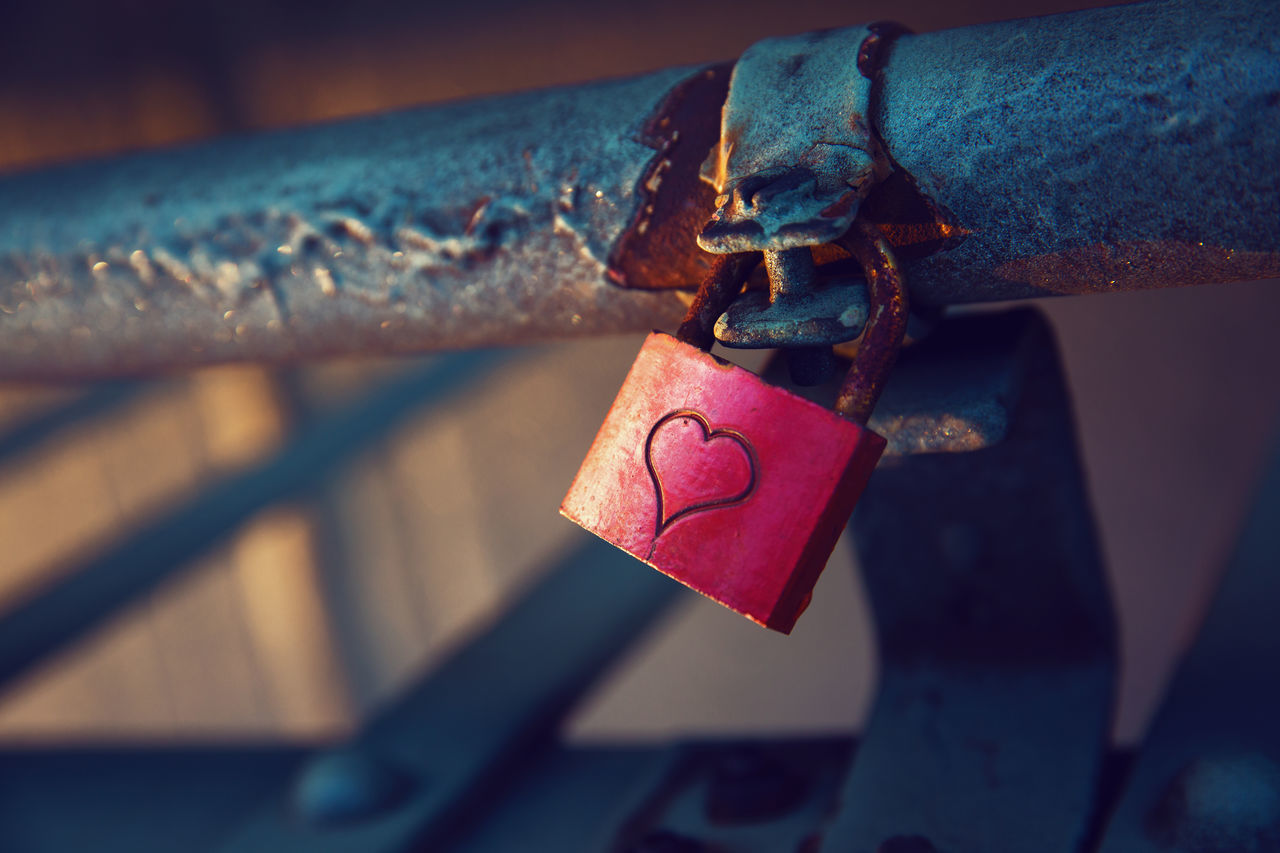Close-Up Of Padlock With Heart Shape Attached On Metallic Railing