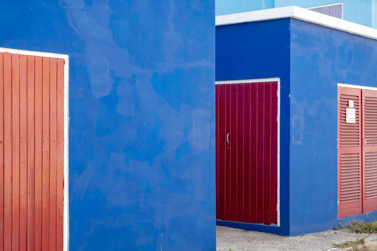 Doors Red Stripes Wall White Frame Blue Blue Wall Building Building Exterior Colorful Deep Blue Door Geometricity No People Outdoors Red Doors