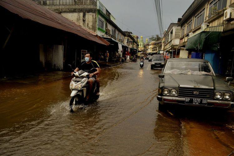 People on wet street amidst buildings during rainy season