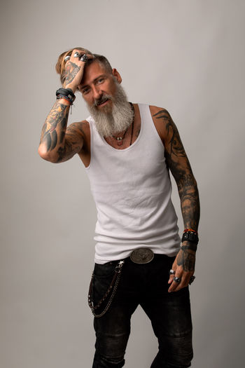 Portrait of a casual bearded hipster isolated on a white background One Person Standing Casual Clothing Indoors  Studio Shot Lifestyles Gray Tattoo Looking Males  Beard Men Model Fashion Isolated Grey Background Jeans Shirt Blackandwhite White Hair Hairstyle Posing Rings Biker