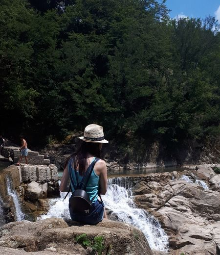 Rear view of young woman with backpack sitting on rock against trees during sunny day