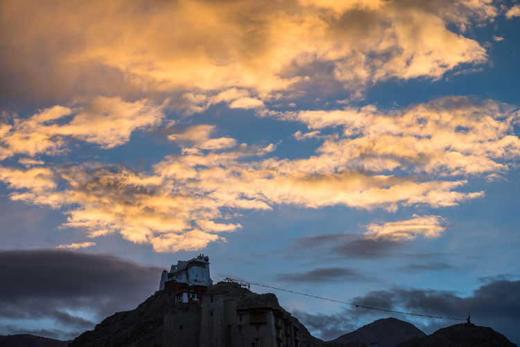 Low angle view of leh palace against cloudy sky at dusk