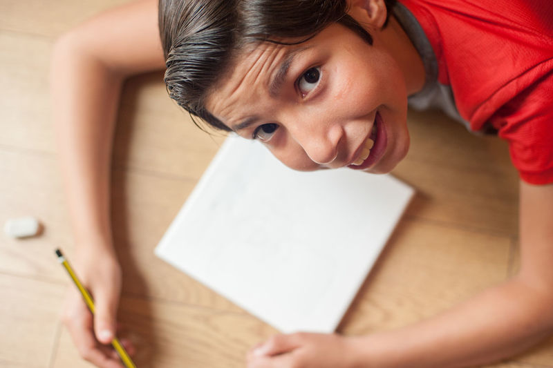 Portrait of boy drawing on book