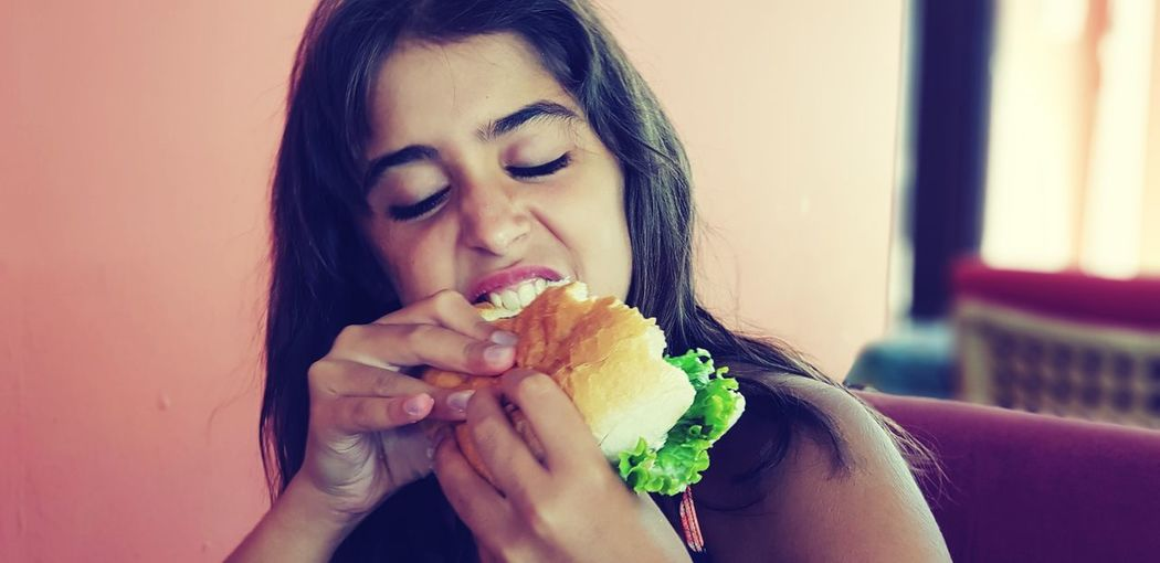 Girl With Eyes Closed Biting Food