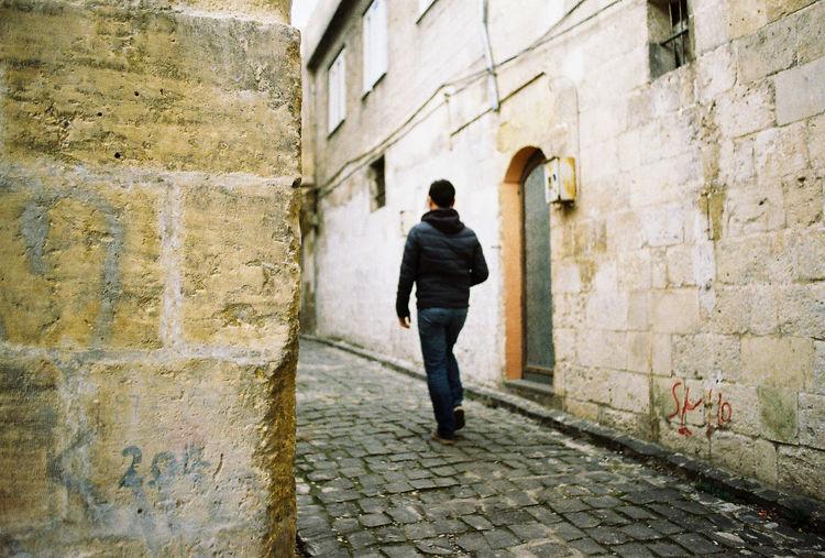 Full length of man walking on sidewalk
