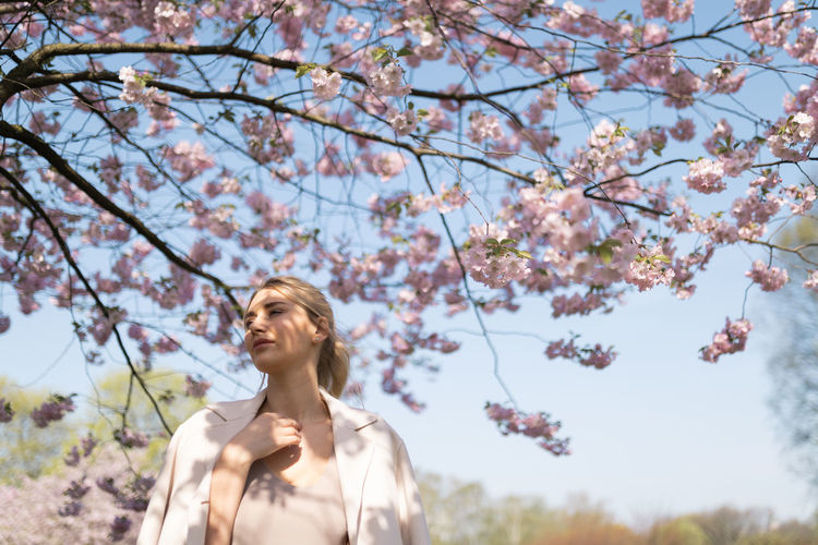 Low angle view of young woman looking at cherry tree