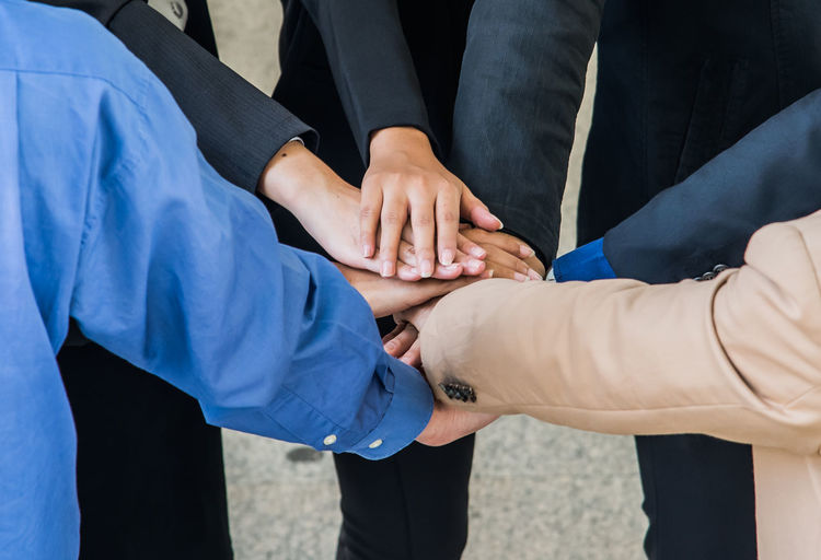 Cropped image of business people stacking hands