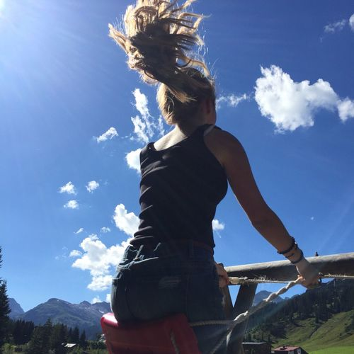 Low angle view of woman enjoying swing against sky