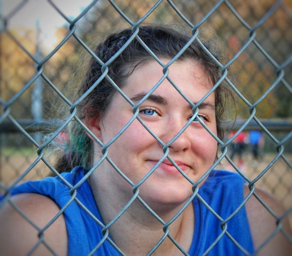 Close-up portrait of  female athlete behind chainlink fence in dugout