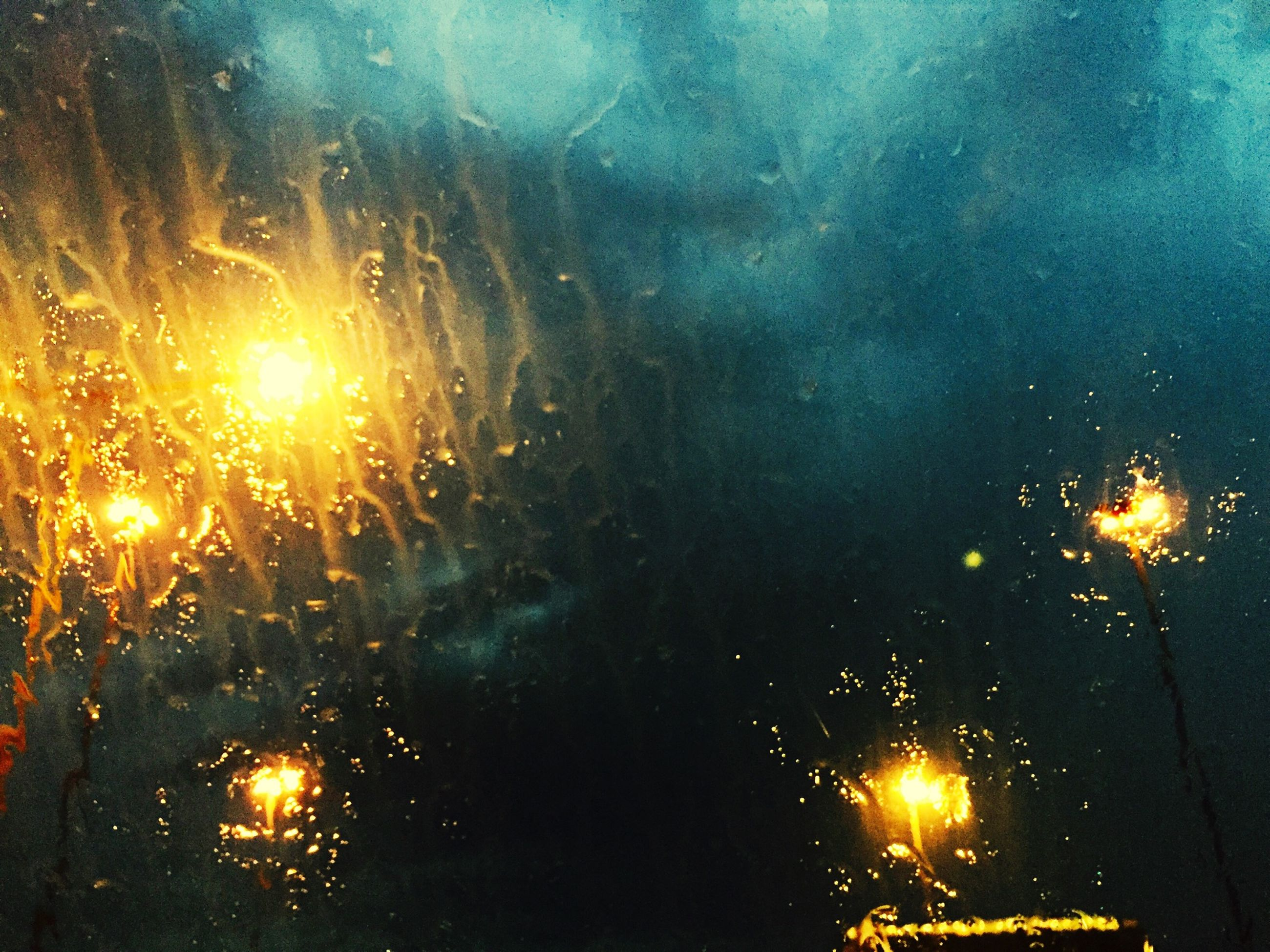 illuminated, night, water, wet, glowing, sky, rain, window, glass - material, transparent, full frame, weather, light - natural phenomenon, no people, backgrounds, drop, lighting equipment, outdoors, dark, reflection