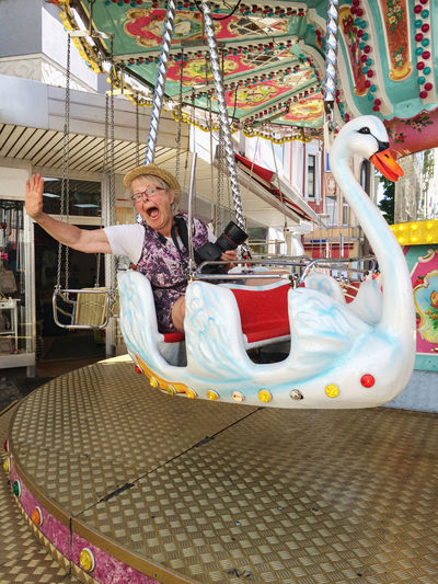 senior woman riding a white swan at funfair Amusement Park Amusement Park Ride Arts Culture And Entertainment Carousel Childhood Day Enjoyment Full Length Fun Happiness Leisure Activity Lifestyles Looking At Camera Merry-go-round One Person Outdoors People Playing Real People Senior Adult Senior Women Sitting Smiling Swan Young At Heart