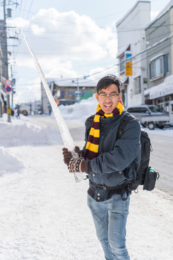 Portrait of man holding icicle while standing on snow